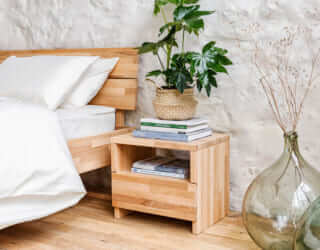 La table de chevet bois massif avec des livres à côté du lit