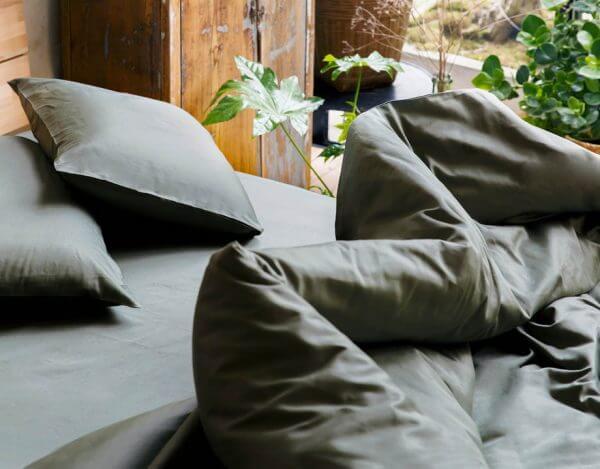 Housse de couette coton bio olive sur matelas avec oreillers