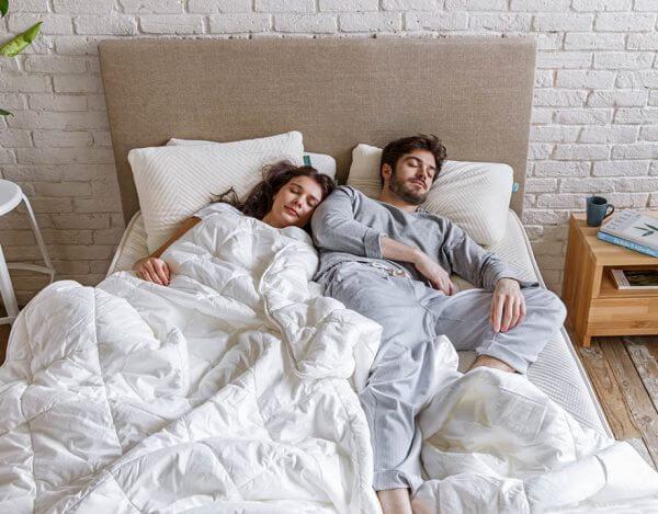 Couple endormi recouvert par leur couette naturelle blanche
