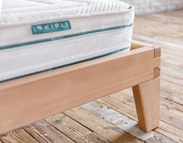 Angle et pied de 20cm du lit bois massif Kipli avec matelas posé dessus
