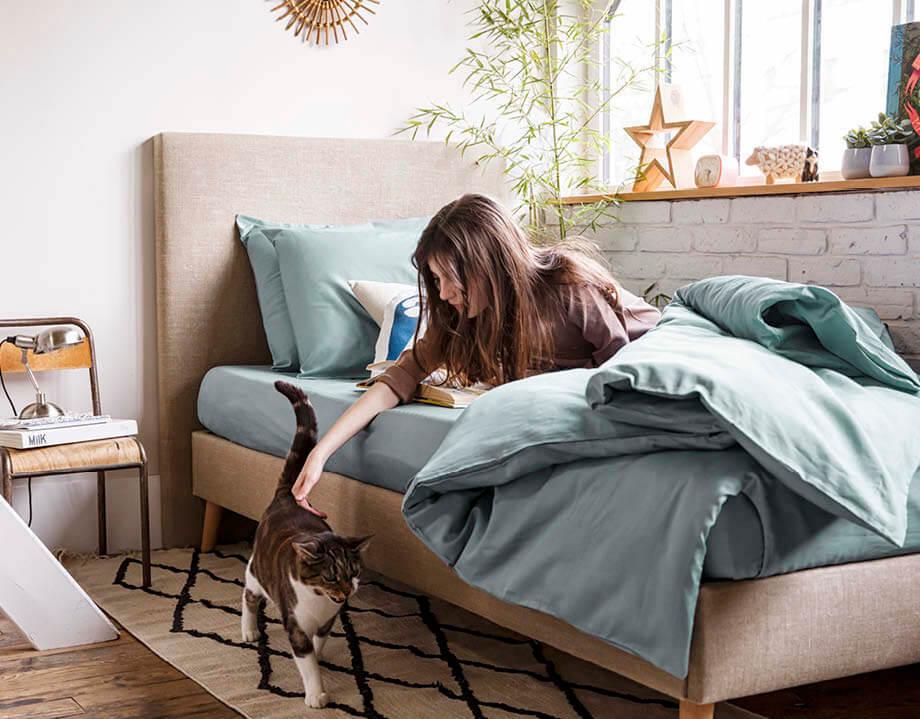 petite fille qui carresse un chat dans son lit parure simple coton bio